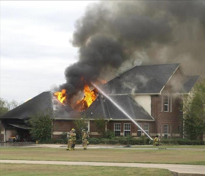 two story house with roof on fire
